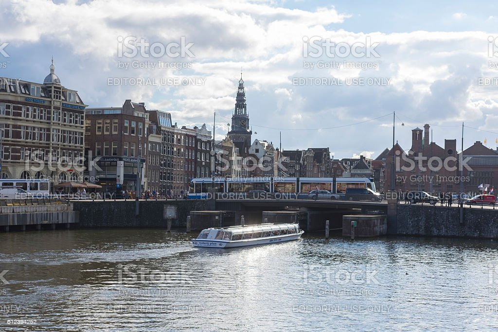 Traditional old buildings and tour boat at an Amsterdam canal stock photo