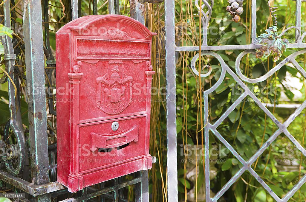 Traditional old English red postbox hang on gate royalty-free stock photo