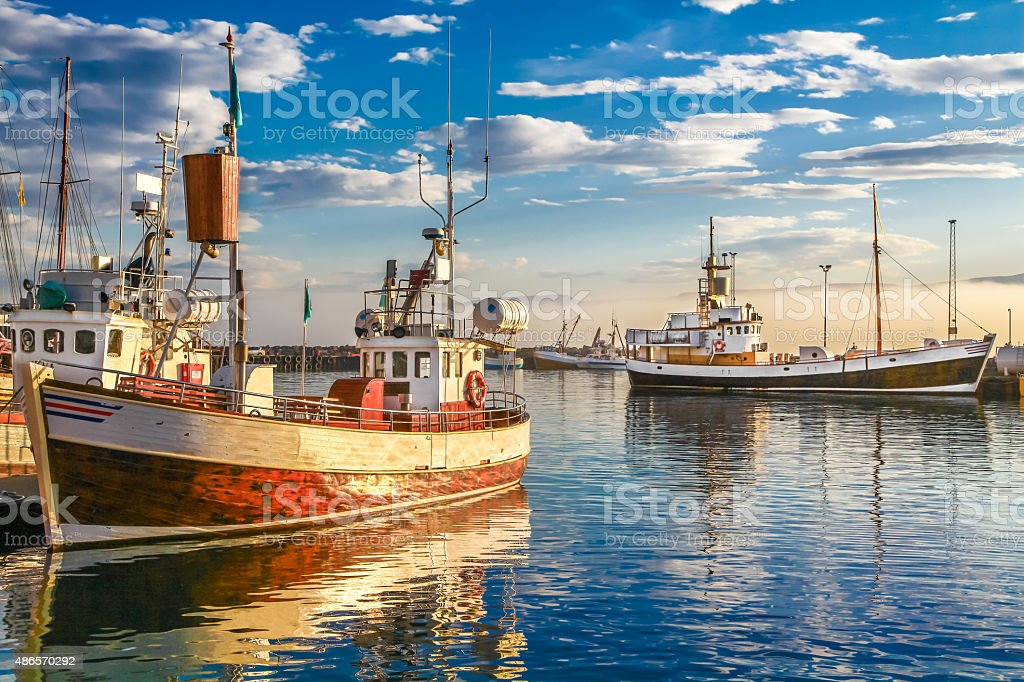 Traditional old wooden fisherman boats in harbor at sunset stock photo