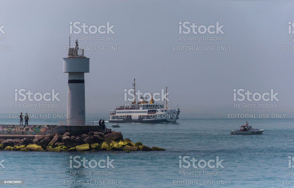 traditional passenger boat and fisherman at coast of bosphorus near kadikoy istanbul turkey stock photo