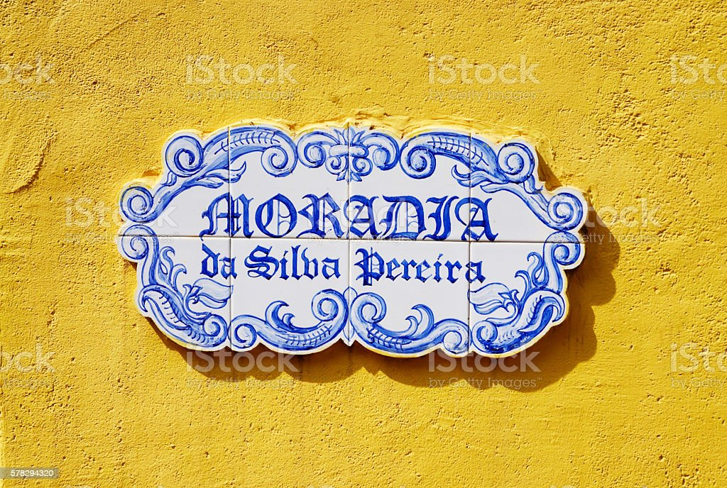 Traditional  plate with  street name on yellow wall,Goa,India stock photo