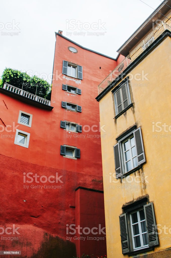 Traditional red, yellow old walls, wooden shutter windows in Bergamo, Italy. stock photo