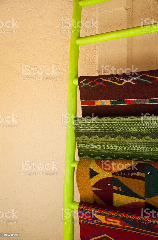 Traditional Rugs Hang on Brilliant Lime Green Ladder, Mexico royalty-free stock photo