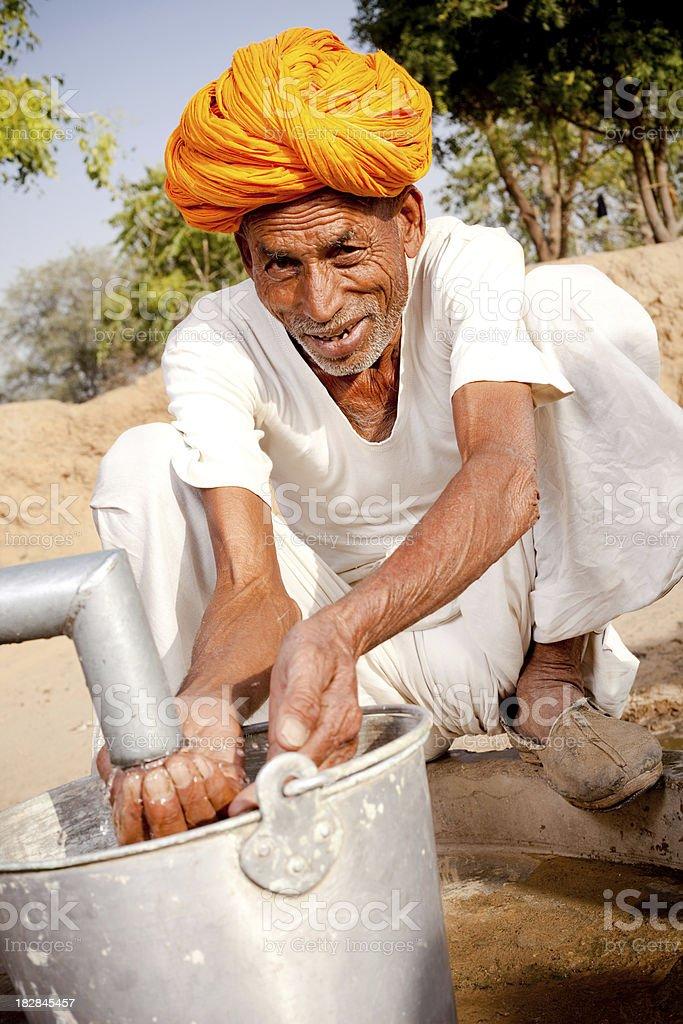 Traditional Rural Indian Senior man drinking water in Rajasthan royalty-free stock photo
