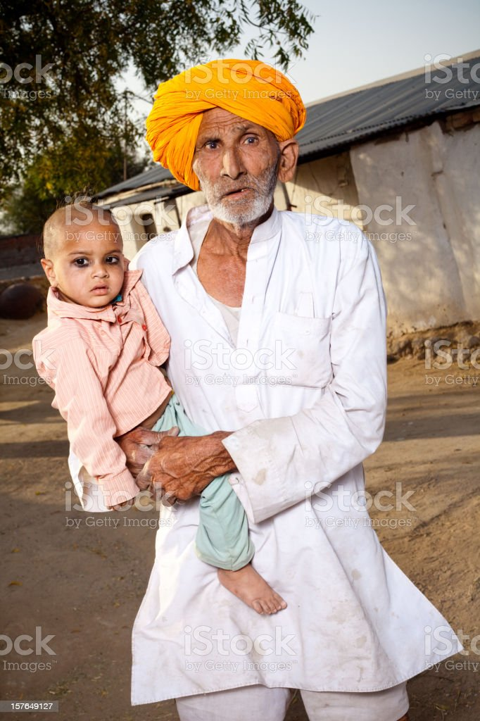 Traditional Rural Indian Senior Man with his Grandson in Rajasthan royalty-free stock photo