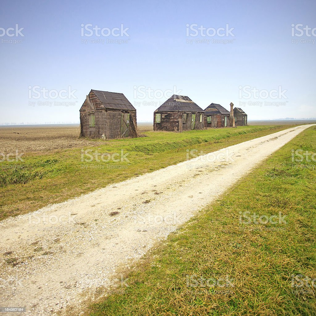 Traditional rural wooden huts in italian countryside. Country road. royalty-free stock photo