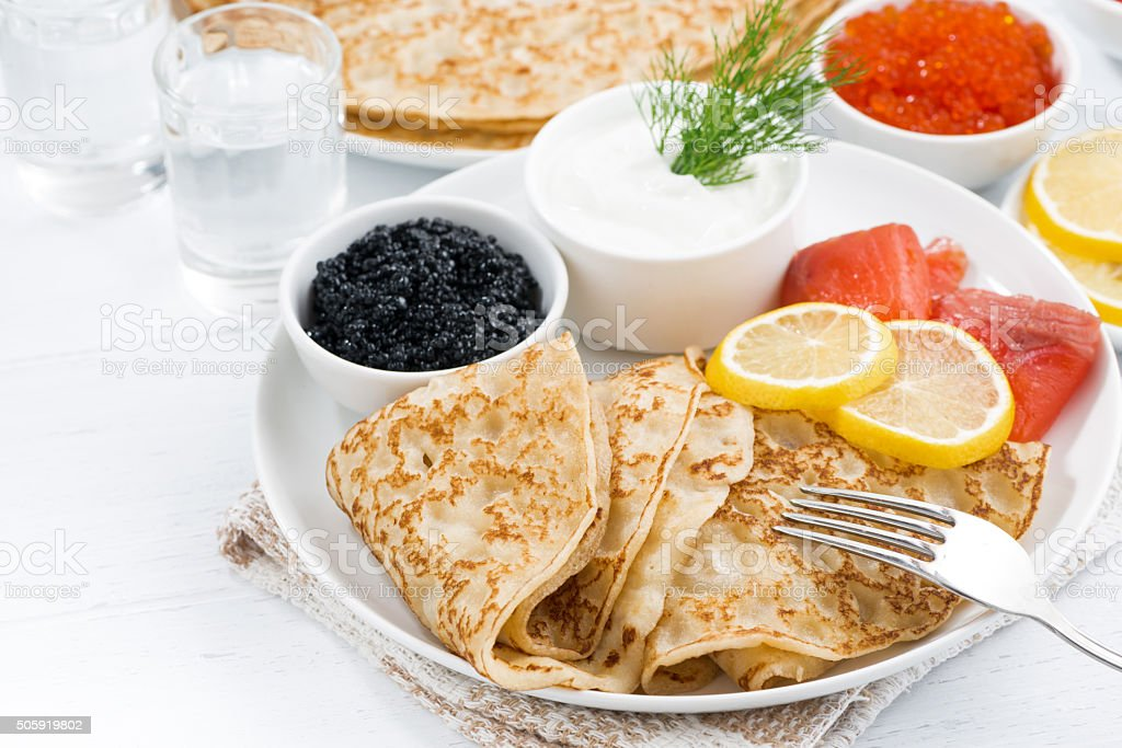 traditional Russian crepes with caviar and salted fish on table stock photo