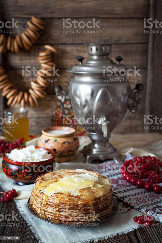Traditional russian pancakes with cottage cheese, milk, bagels and samovar stock photo