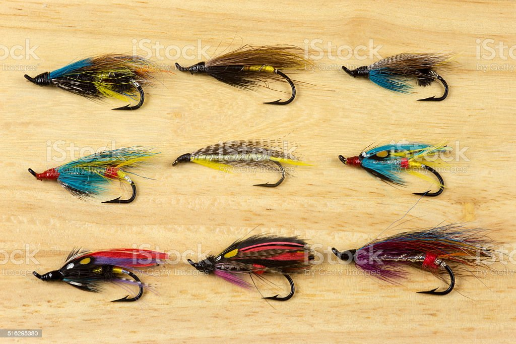 Traditional Salmon Fishing Flies on a Wooden Background stock photo