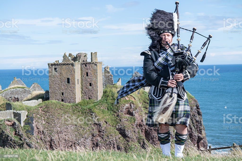 Traditional scottish bagpiper at Dunnottar Castle stock photo