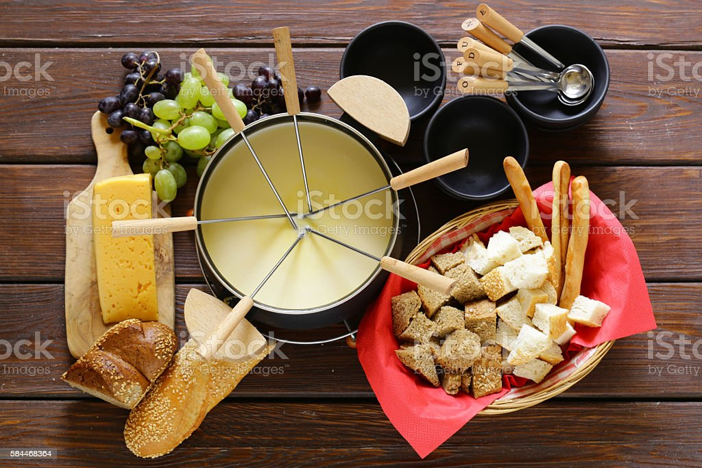 Traditional set of utensils for fondue, with bread, cheese, grapes stock photo
