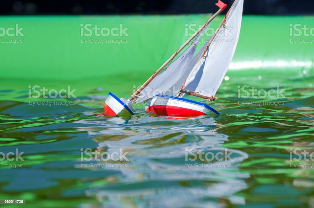 Traditional small wooden sailing boat in the pond of park stock photo