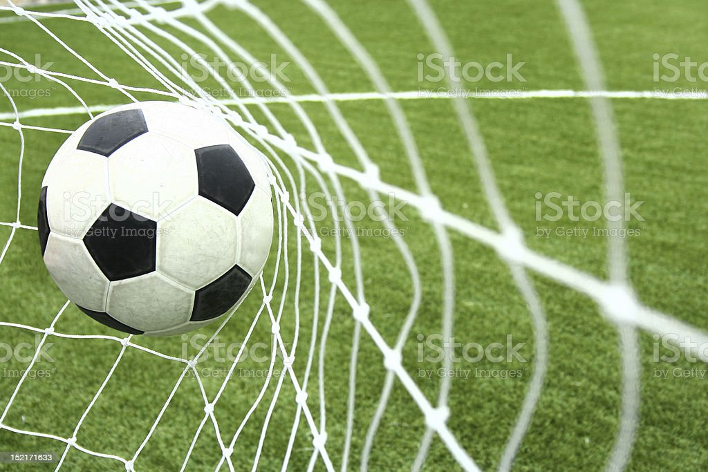 Traditional soccer ball stretches net of goal stock photo
