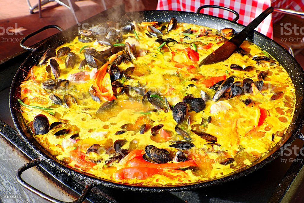 Traditional Spanish street food: seafood paella cooking in pan stock photo