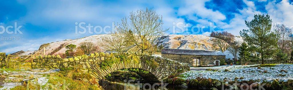 Traditional stone bridge over mountain stream snowy Lake District Cumbria stock photo