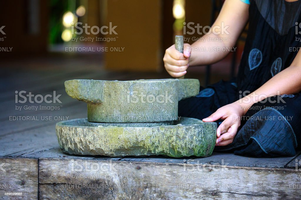 Traditional stone mortar and woman stock photo