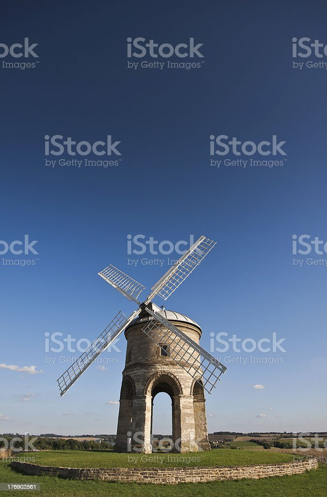 Traditional stone windmill under blue skies stock photo