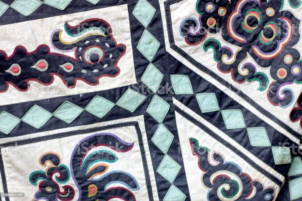 Traditional symbolic ornament on smoth fabric. Animals shapes on clothes of nanai culture stock photo