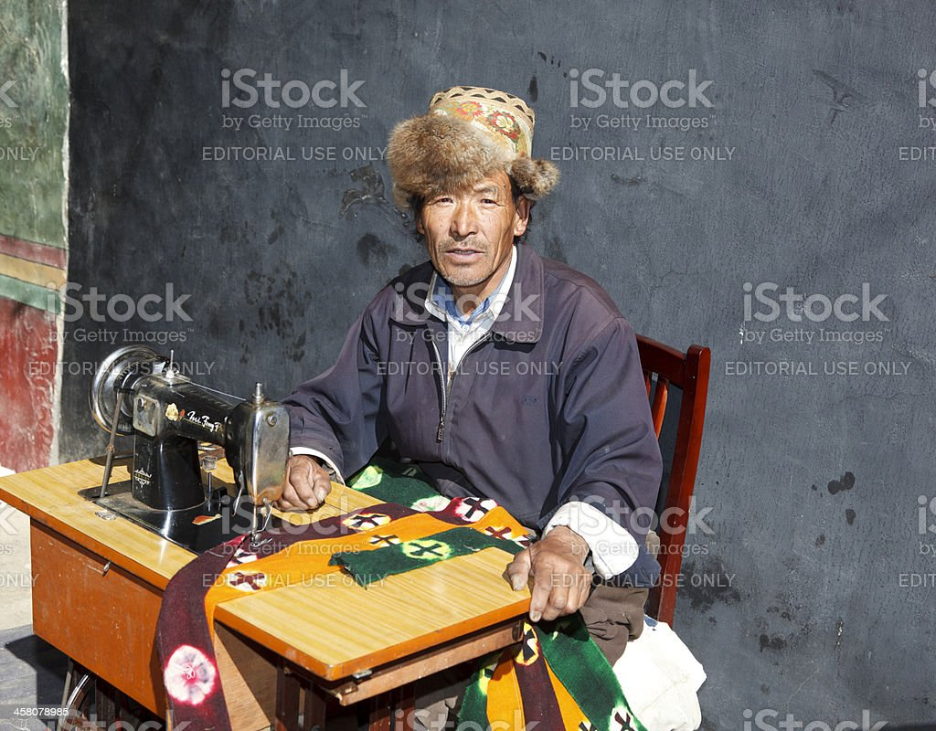Traditional tailor in fur hat Mindroling Monastery Tibet royalty-free stock photo