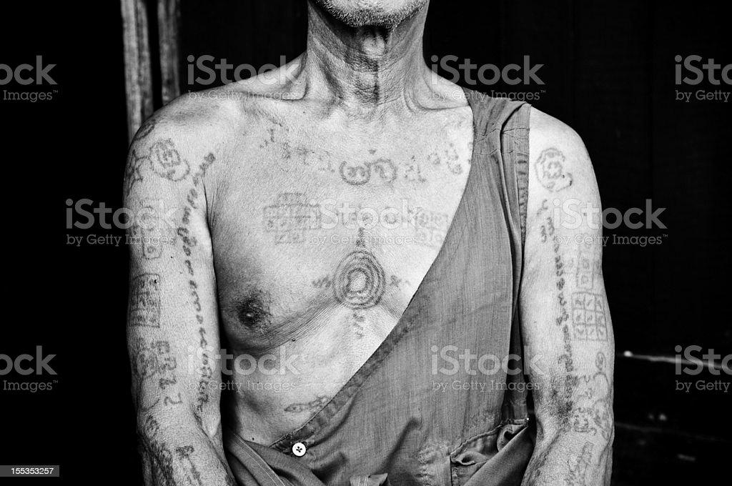 Traditional tattooed torso of a Burmese monk in Mandalay, Myanmar stock photo