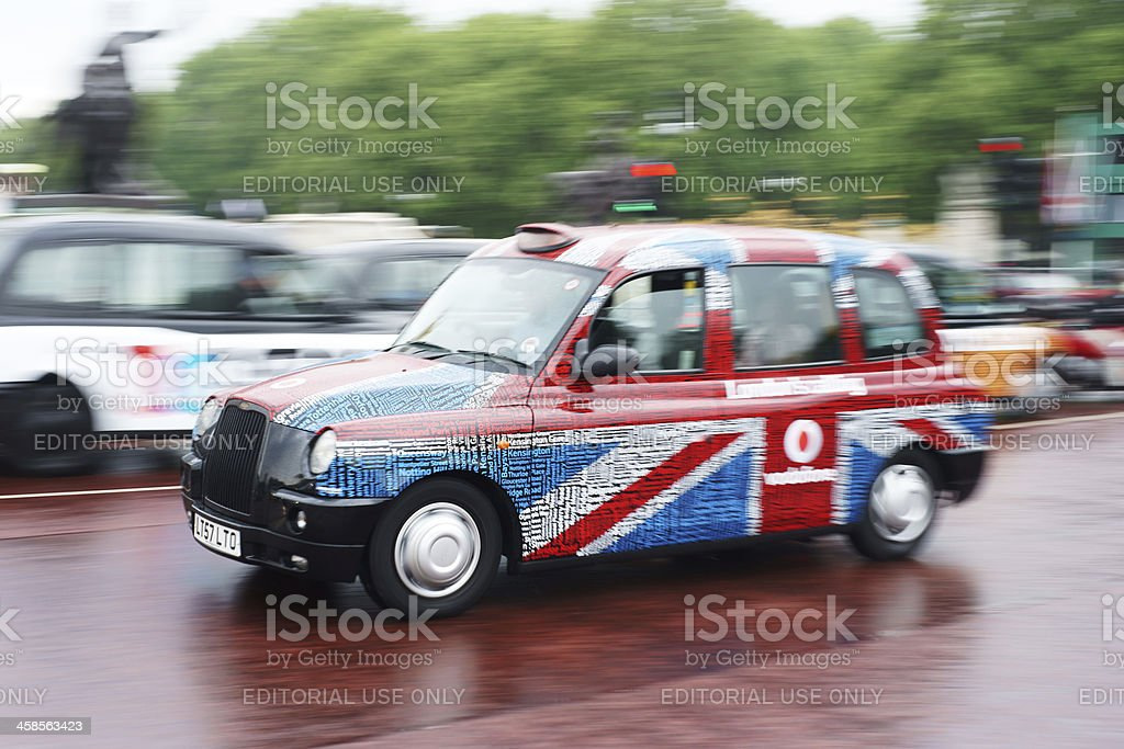 Traditional taxi in Union Jack colors speeding stock photo