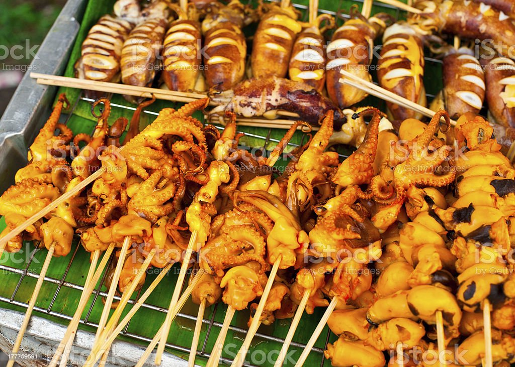 Traditional Thai food at market. Grilled seafood on sticks royalty-free stock photo