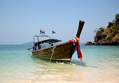 Traditional Thai Longtail Fishing Boat Moored on the Beach