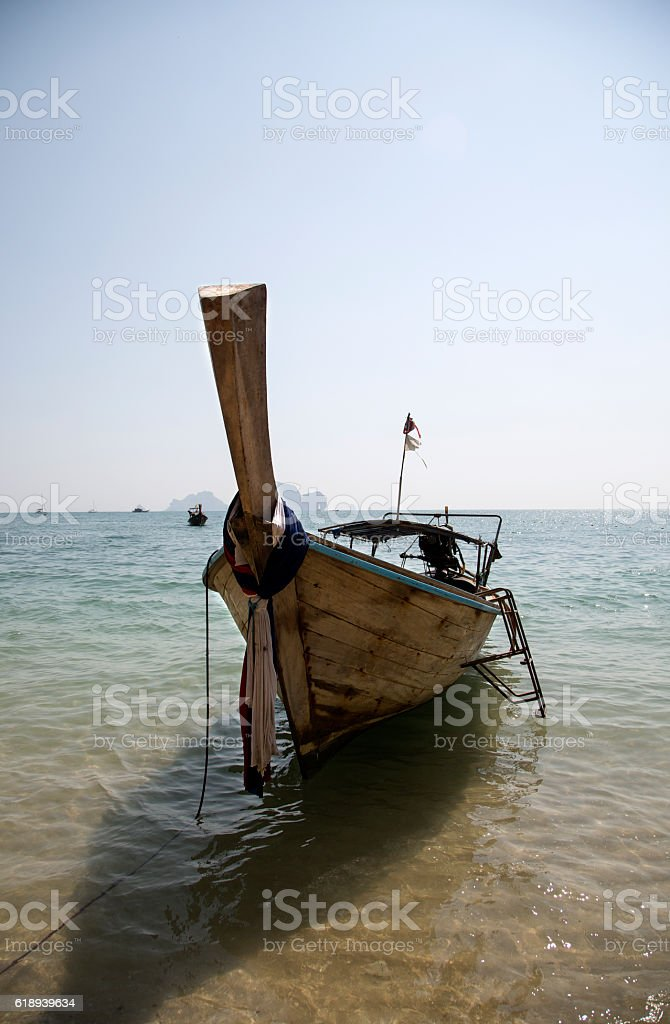 Traditional Thai Longtail Fishing Boat Moored on the Beach stock photo