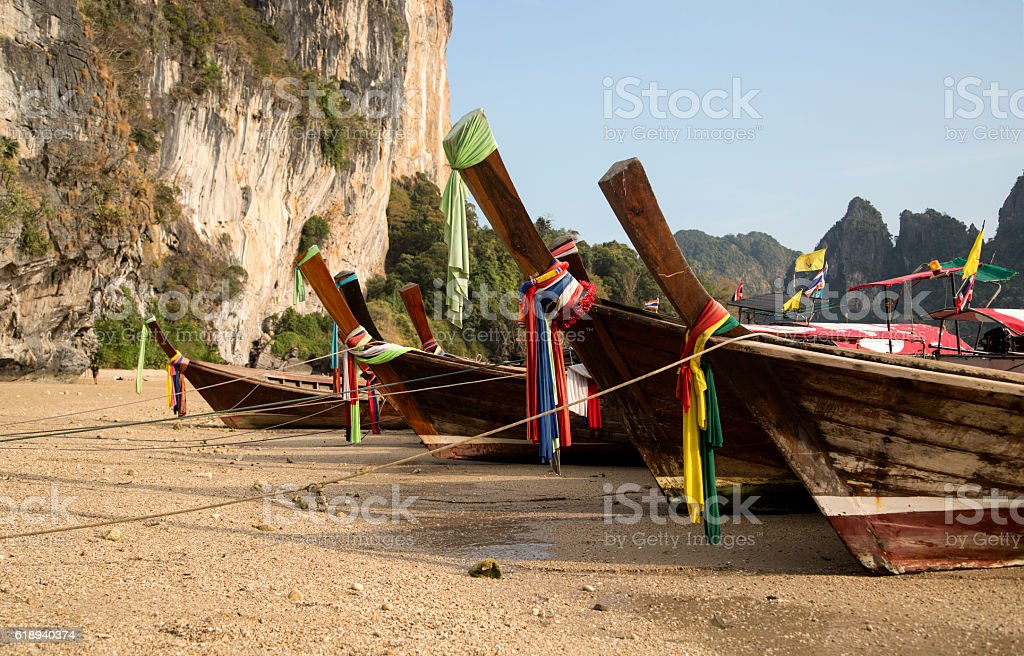 Traditional Thai Longtail Fishing Boats Moored on the Beach stock photo