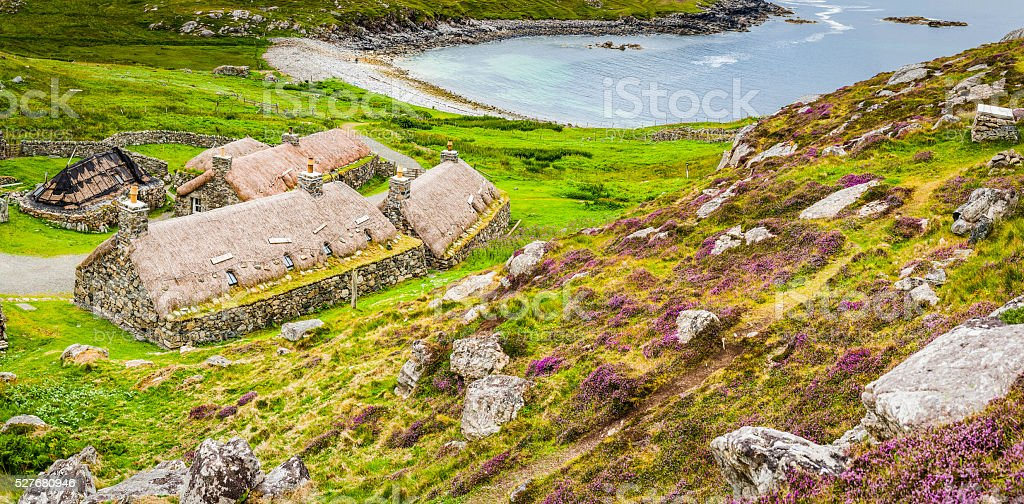 Traditional thatched cottages crofts village homes ocean bay Hebrides Scotland stock photo