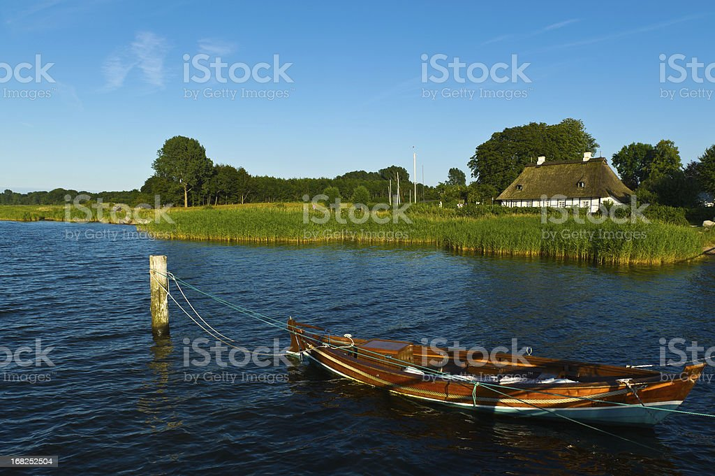 traditional thatched roof house with boat stock photo