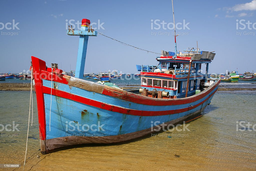 Traditional timber Vietnamese fishing boat on beach stock photo