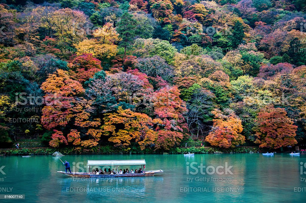 Traditional tourist boat pass on the emerald color Katsura river stock photo