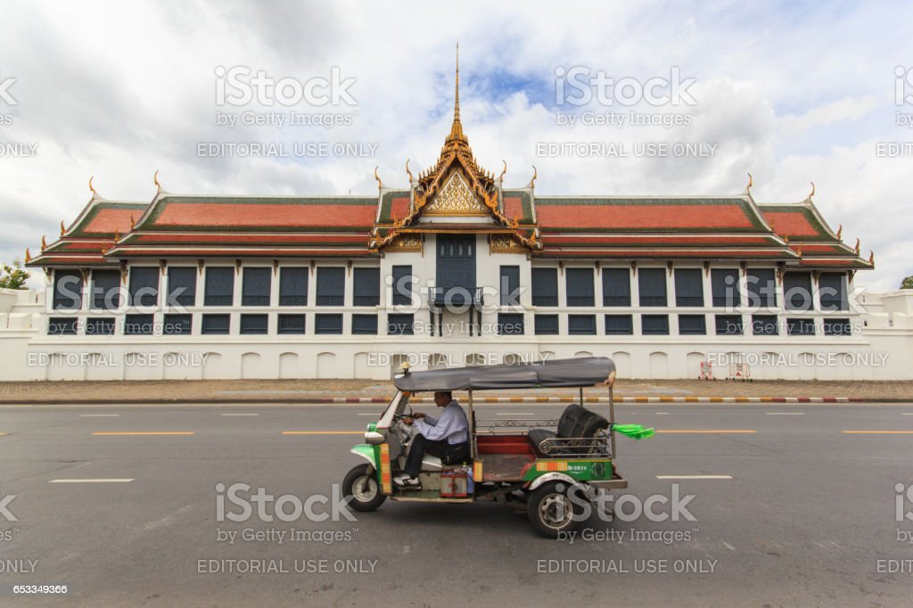 BANGKOK, THAILAND - SEPTEMBER 21, 2013: traditional tuk-tuk on the road in front of the famous Buddhist Temple Wat Phra Kaew, one of the main landmarks of Bangkok, Thailand stock photo