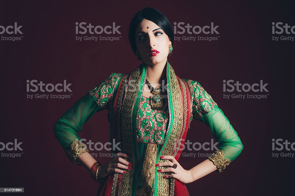 Traditional vintage Bollywood fashion girl against dark red background. stock photo
