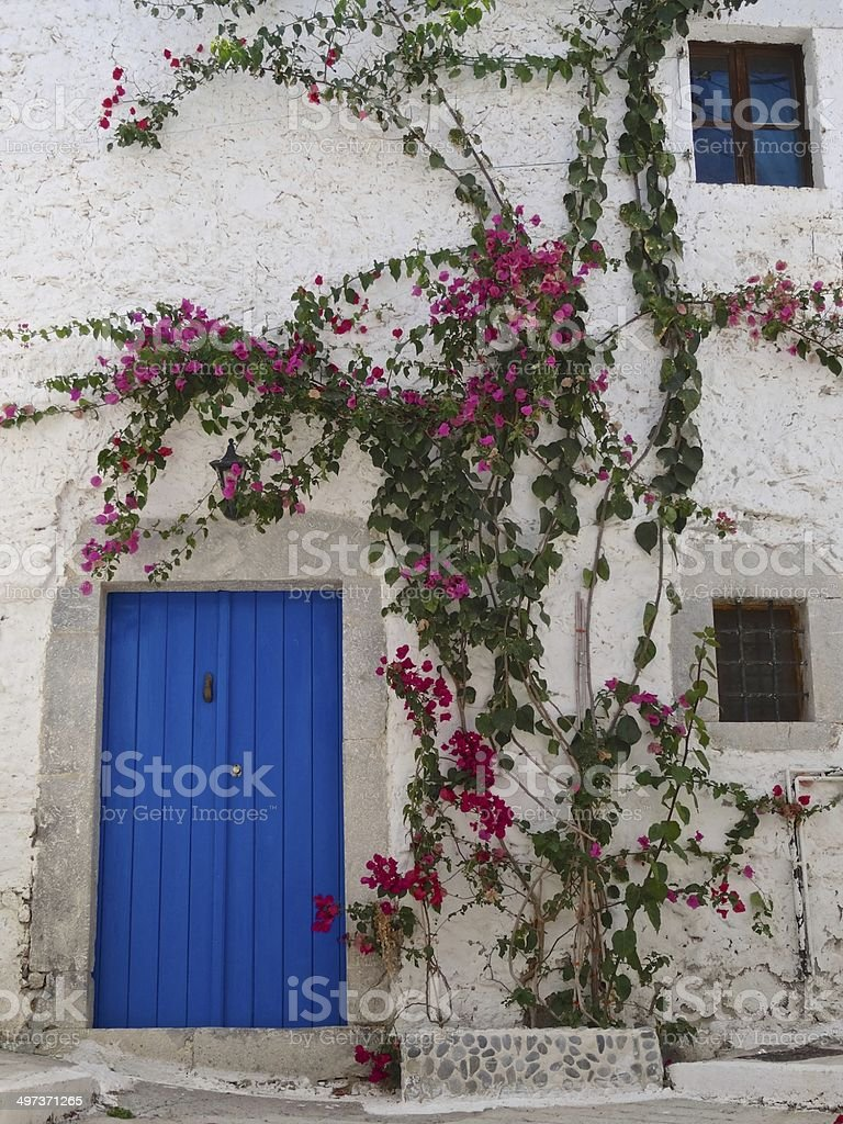 Traditional whitewashed Greek house, with bright climbing flowers royalty-free stock photo