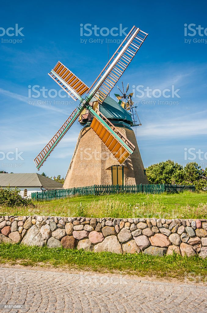 Traditional windmill in beautiful scenery with blue sky and clouds stock photo