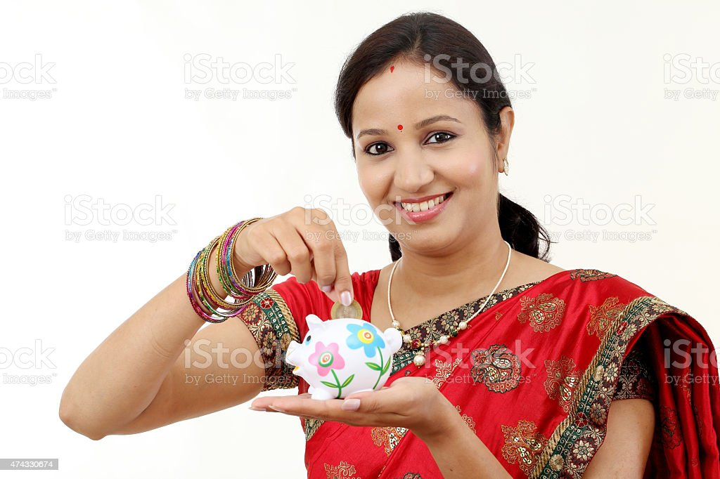 Traditional woman holding a piggy bank and rupee coin stock photo