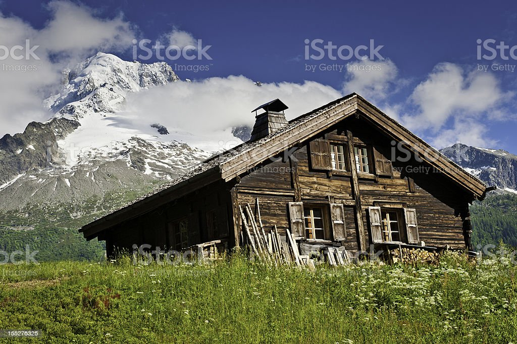 Traditional wooden Alpine chalet summer meadow snowy mountains stock photo
