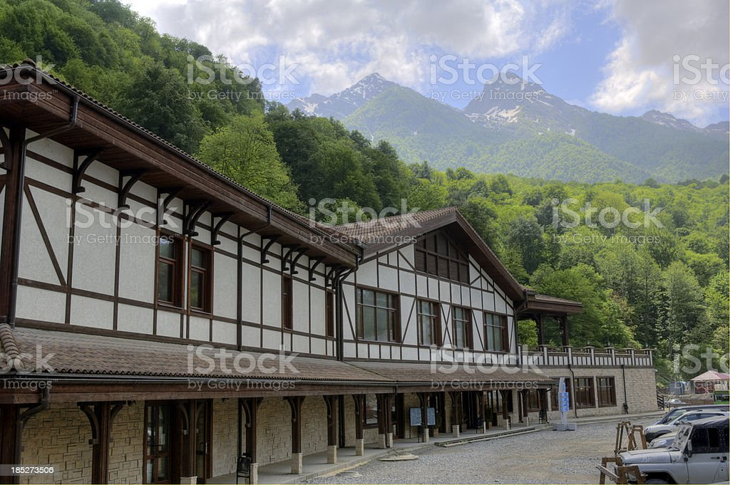 Traditional wooden Alpine hotel summer meadow snowy mountains royalty-free stock photo