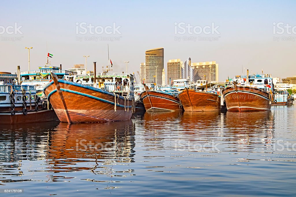 Traditional wooden boats contrast with modern buildings in Dubai stock photo