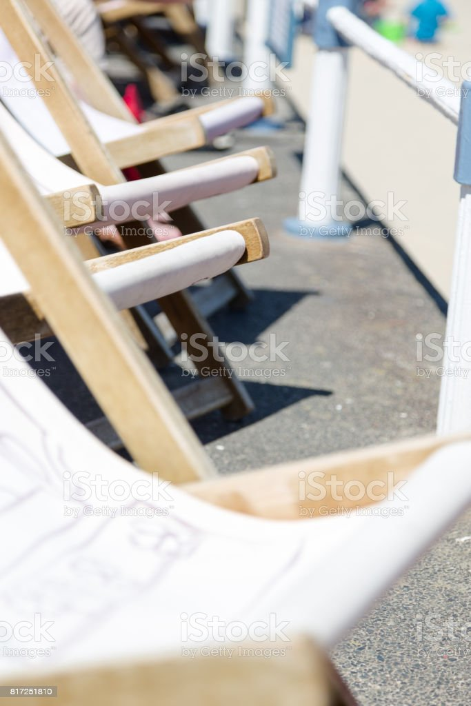 Traditional wooden deck chairs along promenade in Weymouth stock photo