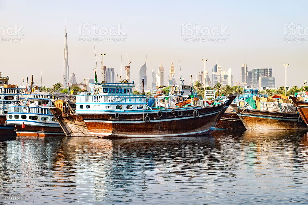 Traditional wooden dhows contrast with modern buildings in Dubai stock photo