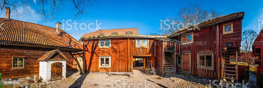 Traditional wooden farm barns cobbled farmyard village agricultural panorama Sweden stock photo
