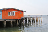 Traditional wooden house of fisherman in orange on concret stilts