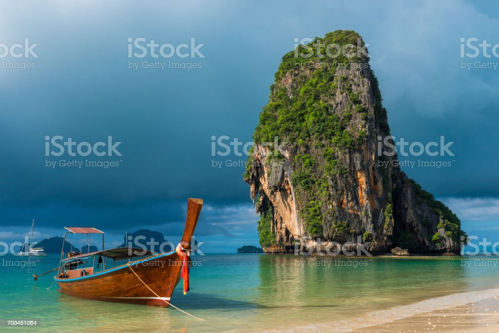Traditional wooden Thai boat near the shore and high cliff stock photo