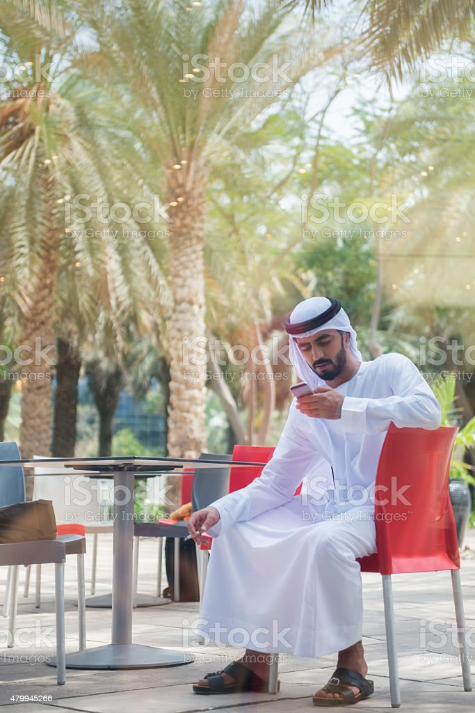 Traditionally Dressed Arab Businessman Texting on Cellphone at Outdoor Patio stock photo