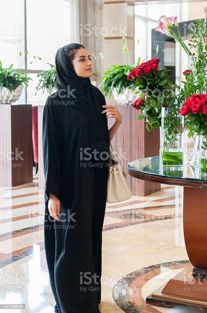 Traditionally Dressed Arabian Woman Walking by Flowers in Hotel Lobby stock photo