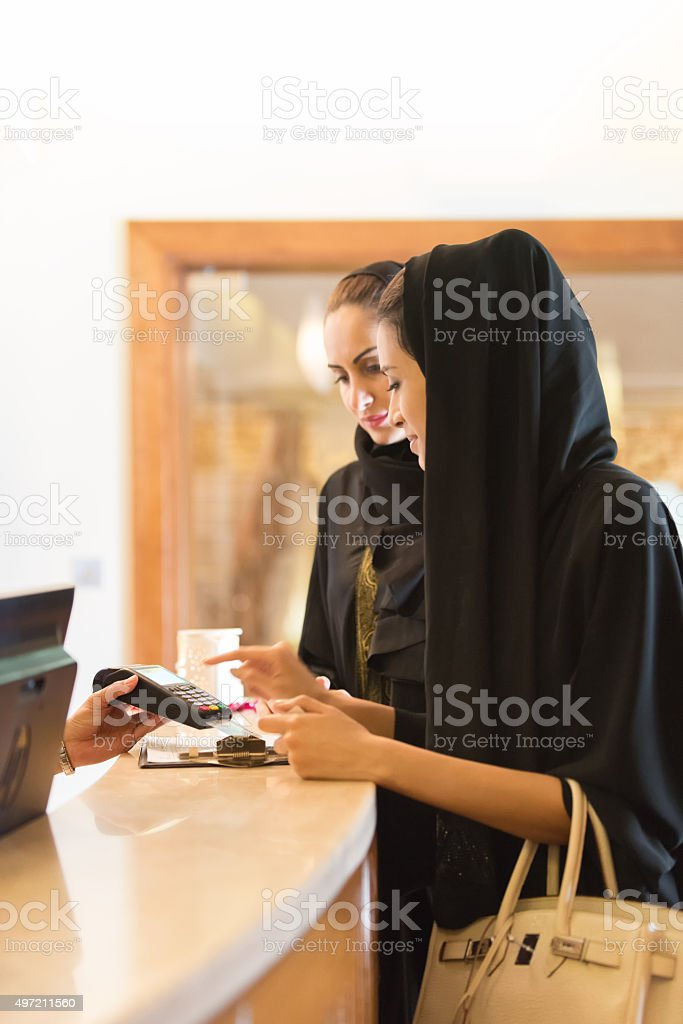 Traditionally Dressed Emirati Woman Paying by Credit Card at Counter stock photo