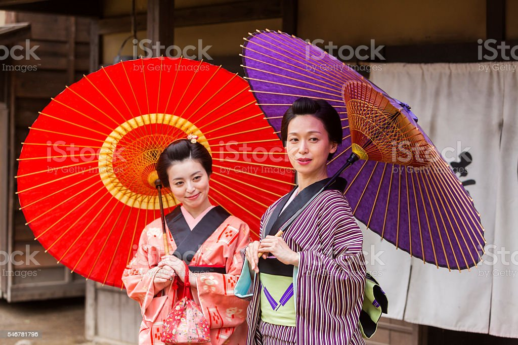 Traditionally Dressed Japanese Women in Kimonos with Umbrellas stock photo